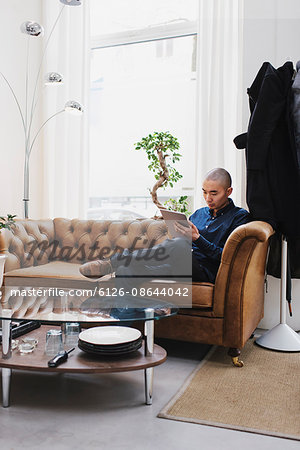 Sweden, Freelancer sitting with digital tablet Stock Photo - Premium Royalty-Free, Image code: 6126-08644042