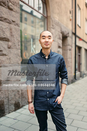 Sweden, Sodermanland, Stockholm, Sodermalm, Smiling young man on sidewalk Stock Photo - Premium Royalty-Free, Image code: 6126-08644046