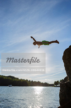 Sweden, Stockholm Archipelago, Teenage boy (16-17) jumping off cliff Stock Photo - Premium Royalty-Free, Image code: 6126-08644616