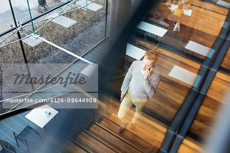 Finland, Young businessman walking upstairs and talking on phone