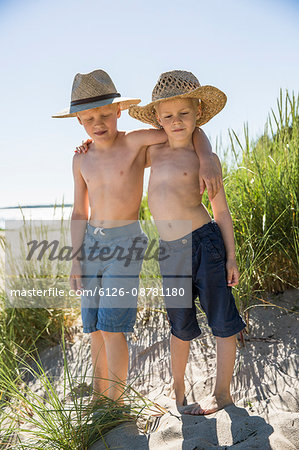Sweden, Gotland, Shirtless boys (6-7, 8-9) in straw hats standing on sand dune at seashore Stock Photo - Premium Royalty-Free, Image code: 6126-08781180