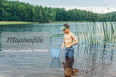 Sweden, Smaland, Mortfors, Kappemalagol, Boy (8-9-) wading and fishing Stock Photo - Premium Royalty-Free, Image code: 6126-08781435