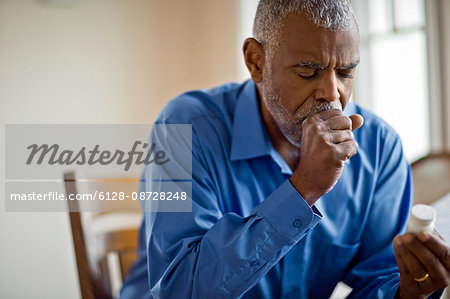 Sick man looks at pill bottle whilst coughing Stock Photo - Premium Royalty-Free, Image code: 6128-08728248