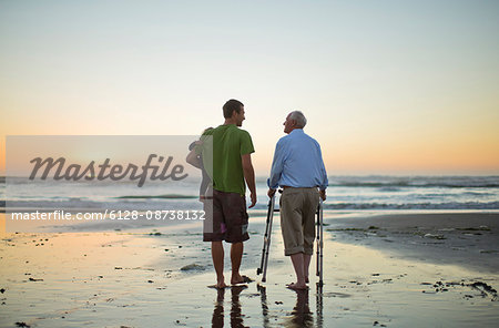 Senior man with a walking aid on the beach with his son and grandchild. Stock Photo - Premium Royalty-Free, Image code: 6128-08738132