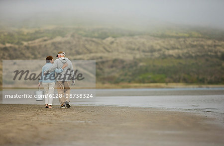 Happy senior couple walking together on a beach. Stock Photo - Premium Royalty-Free, Image code: 6128-08738324