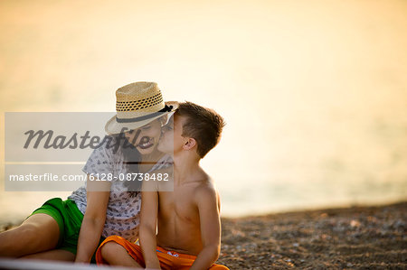 Boy kisses his mother's cheek  on the beach at sunset. Stock Photo - Premium Royalty-Free, Image code: 6128-08738482
