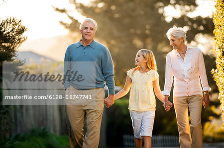 Mature couple walking hand in hand with their young granddaughter. Stock Photo - Premium Royalty-Free, Image code: 6128-08747741