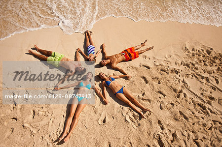 Five laughing people holding hands while lying in the shape of a star on a sandy beach. Stock Photo - Premium Royalty-Free, Image code: 6128-08747913