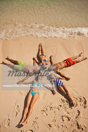 Five laughing people holding hands while lying in the shape of a star on a sandy beach. Stock Photo - Premium Royalty-Free, Image code: 6128-08747916