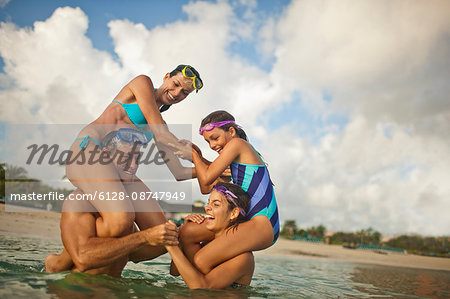Family members having fun playing in waist deep water on a beach. Stock Photo - Premium Royalty-Free, Image code: 6128-08747949