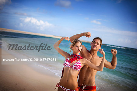 Happy young couple flexing their muscles on a beach. Stock Photo - Premium Royalty-Free, Image code: 6128-08747951