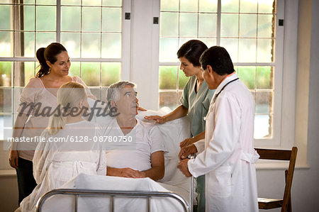 Elderly man receiving a hospital visit from his family. Stock Photo - Premium Royalty-Free, Image code: 6128-08780750