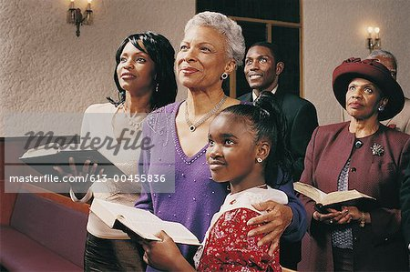 Family Standing in Church Pews Holding Bibles and Listening to a Service Stock Photo - Premium Royalty-Free, Image code: 613-00455836