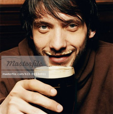 Young Man Enjoying a Drink of Stout in a Pub Stock Photo - Premium Royalty-Free, Image code: 613-00534911