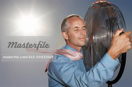 Hot, Relieved Businessman Holding an Electric Fan Stock Photo - Premium Royalty-Free, Image code: 613-00632569