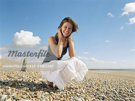 Young woman crouching on beach, smoothing hair and smiling, portrait Stock Photo - Premium Royalty-Free, Image code: 613-00811142
