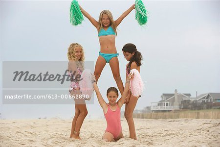 Four girls (8-12) practicing cheerleading formation on beach, portrait Stock Photo - Premium Royalty-Free, Image code: 613-00862890