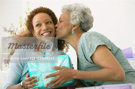 Mother kissing adult daughter, holding present Stock Photo - Premium Royalty-Free, Image code: 613-00998542