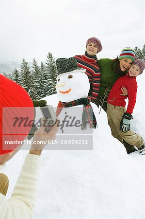 Man taking picture of family by snowman with digital camera Stock Photo - Premium Royalty-Free, Image code: 613-00999231