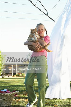 Girl (10-12) holding cat by washing line, portrait, low angle view Stock Photo - Premium Royalty-Free, Image code: 613-01034201