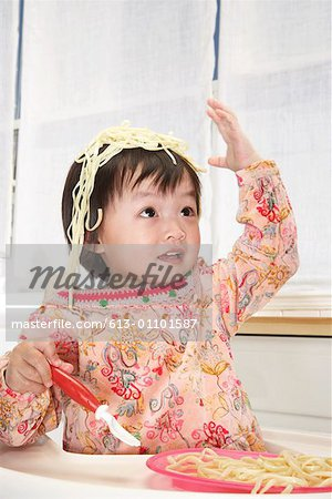 Baby girl (18-24 months) in high chair with spaghetti on head Stock Photo - Premium Royalty-Free, Image code: 613-01101587