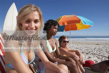 Young woman, teenage girl and boy (15-17)on beach, woman smiling