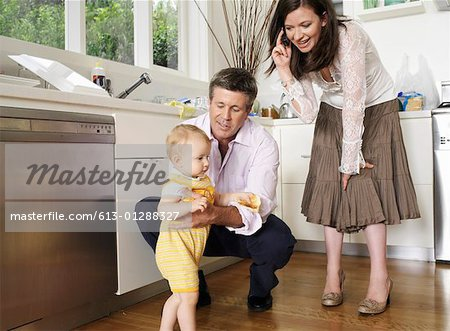 Parents looking at daughter (9-12 months) walking in kitchen Stock Photo - Premium Royalty-Free, Image code: 613-01288327