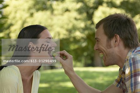 Couple relaxing in park, man feeding woman grape, both laughing Stock Photo - Premium Royalty-Free, Image code: 613-01290499