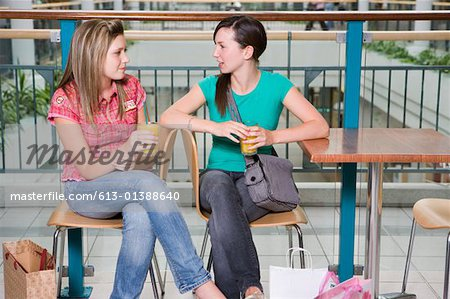 Teenage girls (15-17) with drinks at cafe table in shopping centre Stock Photo - Premium Royalty-Free, Image code: 613-01388640