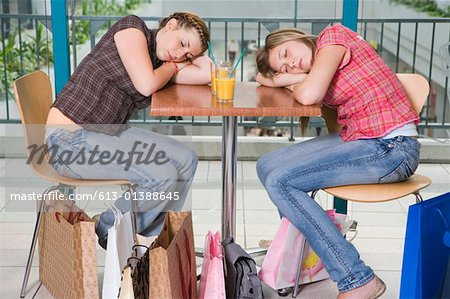 Teenage girls (15-17) asleep at cafe table, shopping bags around feet Stock Photo - Premium Royalty-Free, Image code: 613-01388645