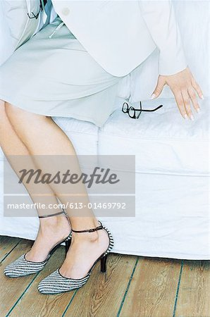 Woman crouching to sit, glasses on sofa, close-up Stock Photo - Premium Royalty-Free, Image code: 613-01469792