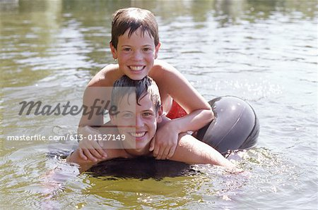 Two brothers (11-14) on inflatable ring in lake, smiling, portrait Stock Photo - Premium Royalty-Free, Image code: 613-01527149