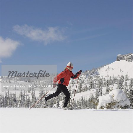 USA, California, young woman cross-country skiing, side view Stock Photo - Premium Royalty-Free, Image code: 613-01533383