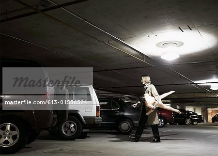 Young businessman carrying blow- up doll in parking garage, side view Stock Photo - Premium Royalty-Free, Image code: 613-01536524