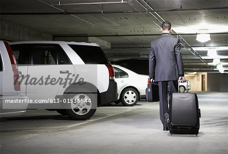 Young businessman with luggage in parking garage, rear view Stock Photo - Premium Royalty-Free, Image code: 613-01536544