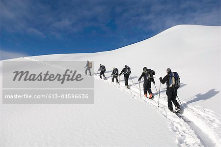 Group of people climbing in snow, low angle view, rear view Stock Photo - Premium Royalty-Free, Image code: 613-01596636