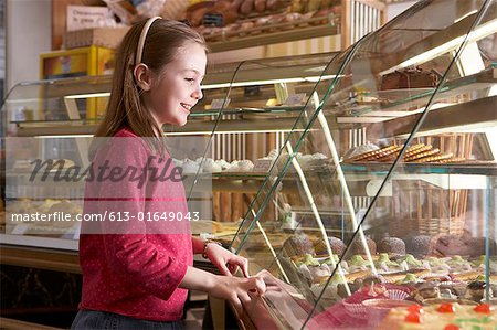 Young girl (9-11) looking at cakes in display cabinets, side view Stock Photo - Premium Royalty-Free, Image code: 613-01649043