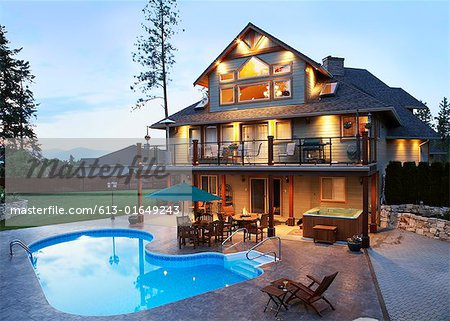 canada british columbia kelowna exterior of large illuminated house by swimming pool at