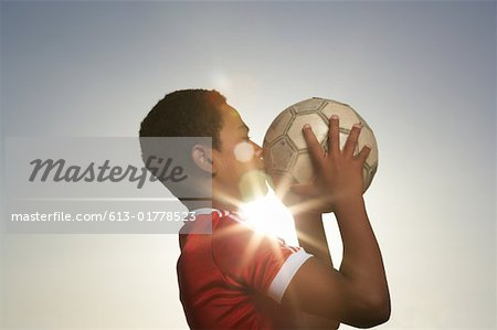 Profile of boy (12-13) kissing football, lens flare Stock Photo - Premium Royalty-Free, Image code: 613-01778523