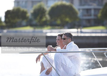 Mature couple sitting on yacht's bow, drinking wine Stock Photo - Premium Royalty-Free, Image code: 613-01779710