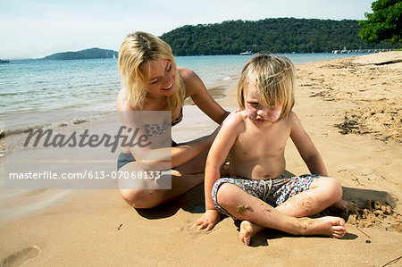 Mother putting sunscreen on her son at the beach Stock Photo - Premium Royalty-Free, Image code: 613-07068133