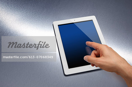 Electronic tablet device on brushed metal Stock Photo - Premium Royalty-Free, Image code: 613-07068349