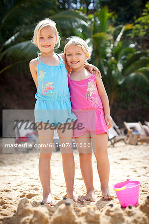 girls standing in front of sand castle on beach Stock Photo - Premium Royalty-Free, Image code: 613-07454000