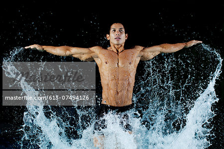Fit man jumping out of water Stock Photo - Premium Royalty-Free, Image code: 613-07454126