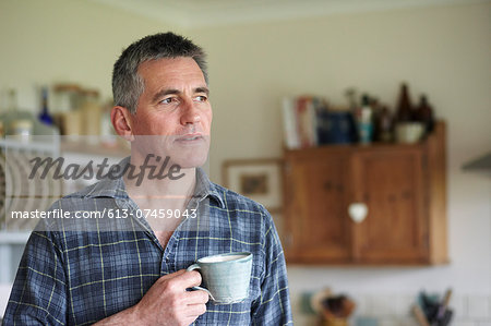 Man holding coffee cup in kitchen Stock Photo - Premium Royalty-Free, Image code: 613-07459043