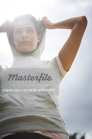 Female putting on hoodie Stock Photo - Premium Royalty-Free, Image code: 613-07492473