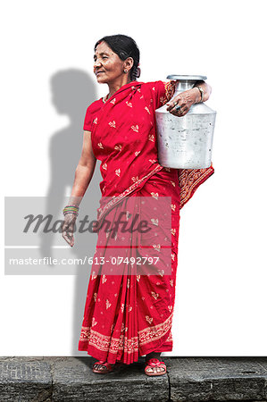 Lady in red saree carrying a bucket of water Stock Photo - Premium Royalty-Free, Image code: 613-07492797