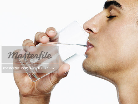 Portrait of man drinking a glass of water Stock Photo - Premium Royalty-Free, Image code: 613-07673657