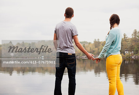 Teen couple holding hands by a lake Stock Photo - Premium Royalty-Free, Image code: 613-07673901