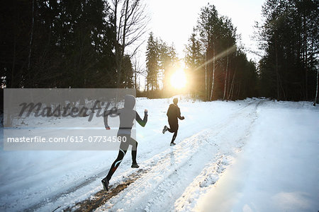 Two runners on snowy forest road in the morning Stock Photo - Premium Royalty-Free, Image code: 613-07734580